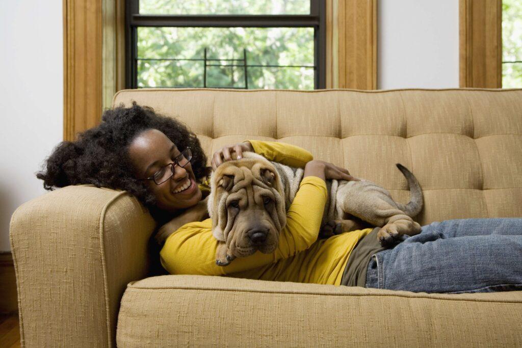 Uma mulher está deitada em sofá, com cão deitado em seu colo. Ambos estão em uma sala comum. A mulher usa uma blusa amarela.