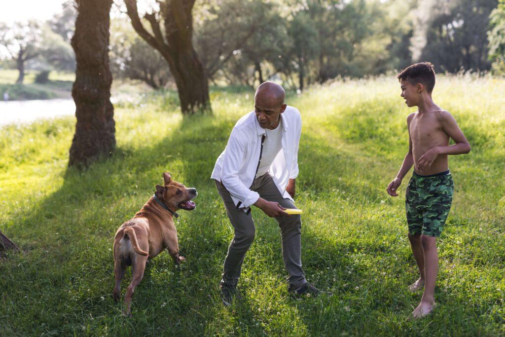 Um homem adulto e uma garoto brincam de frisbee com um cão em um campo com grama e árvores.